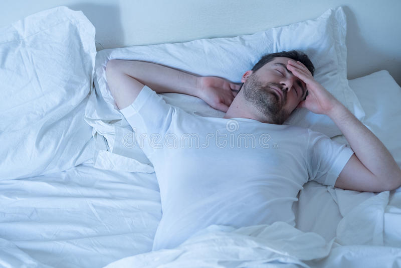 Uomo turbato che prova a dormire nel suo letto alla notte fotografia stock libera da diritti