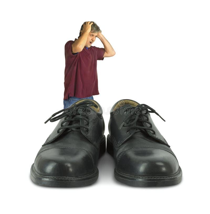 Uomo turbato che sta davanti ad alcune grandi scarpe per riempire fotografia stock