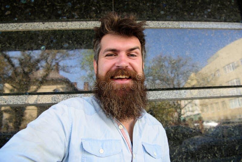 Uomo, turista con la barba e baffi sul fronte allegro e sorridente, fondo di marmo nero Concetto di Vlogging hipster immagine stock