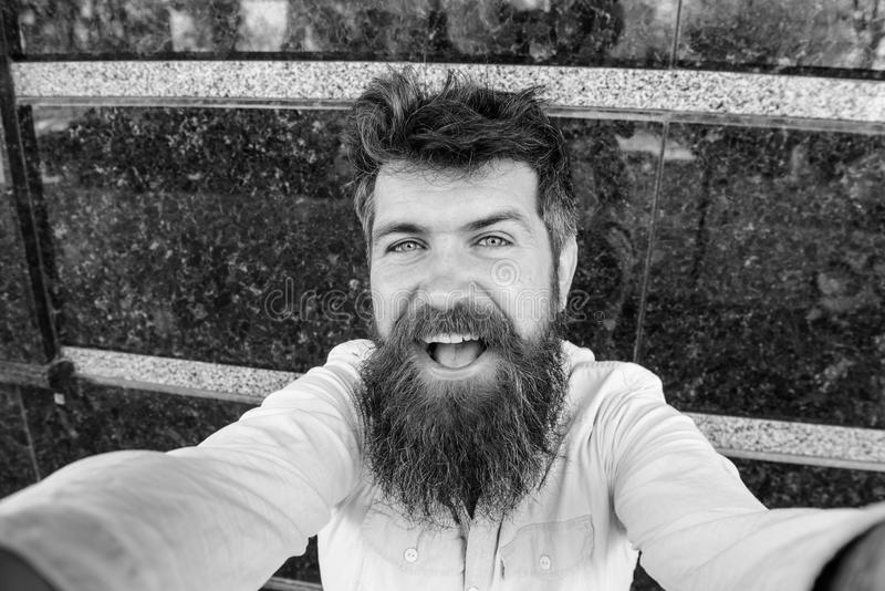 Uomo, turista con la barba e baffi sul fronte allegro e sorridente, fondo di marmo nero Pantaloni a vita bassa, turista con scomp immagine stock libera da diritti