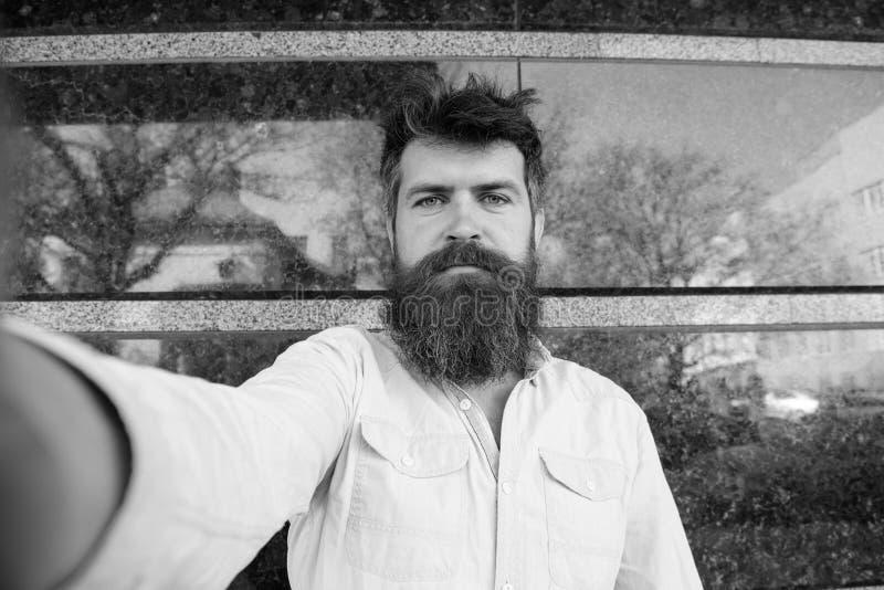 Uomo, turista con la barba e baffi sul fronte calmo e serio, fondo di marmo nero Concetto di Vlogging Pantaloni a vita bassa, tur immagine stock