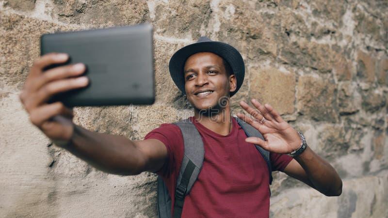 Uomo turistico afroamericano felice che ha video chiacchierata online facendo uso del computer della compressa mentre viaggiando  immagini stock