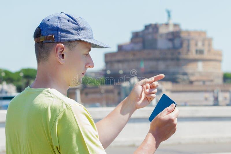Uomo turistico che esamina schermo del computer della compressa il fondo della via di estate di Roma immagine stock libera da diritti