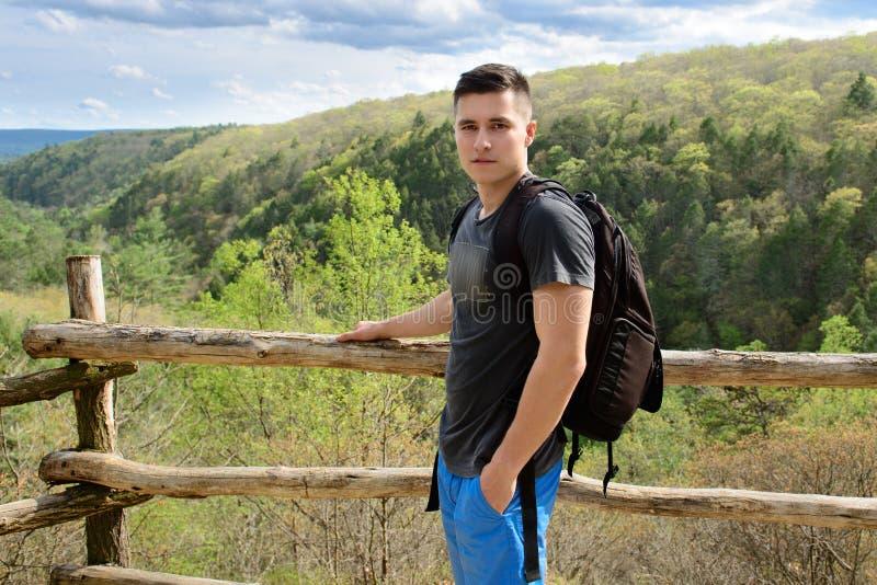 Uomo turistico che viaggia con lo zaino in montagne e la traccia di escursione della foresta all'ora legale fotografia stock