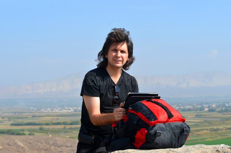 Uomo turistico con capelli lunghi che cercano informazioni in un computer della compressa fotografia stock