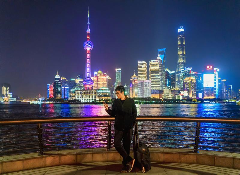 Uomo turistico facendo uso di uno smartphone vicino a Bund nella citt? di Shanghai, Cina nel viaggio di viaggio, nella vacanza, o immagine stock