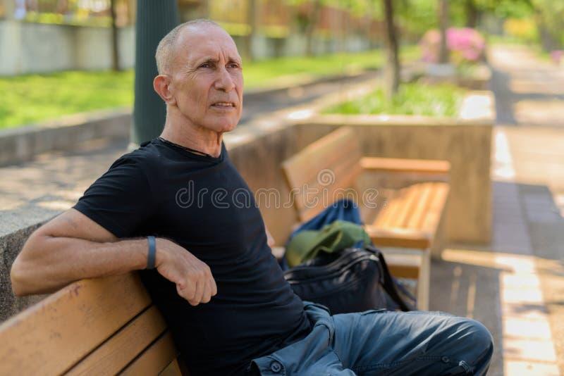 Uomo turistico senior calvo che pensa sul banco di legno a pacifico fotografia stock