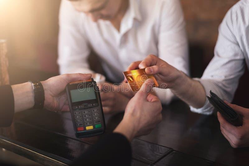 Uomo ubriaco che paga via la carta di credito nella barra fotografie stock libere da diritti