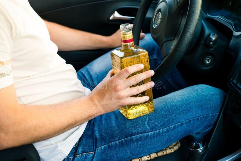 Uomo ubriaco che si siede dietro la ruota di un'automobile e di un alcoho bevente fotografia stock libera da diritti