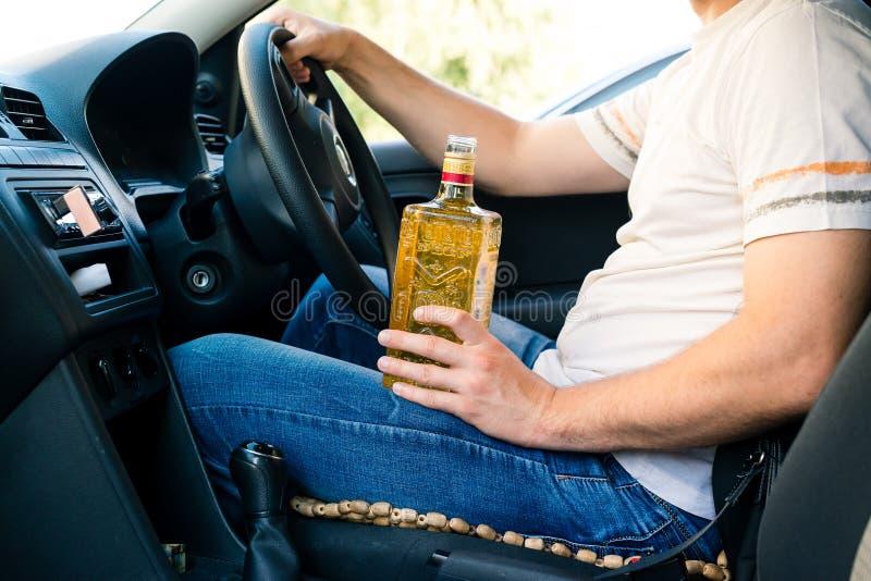 Uomo ubriaco che si siede dietro la ruota di un'automobile e di un alcoho bevente fotografia stock