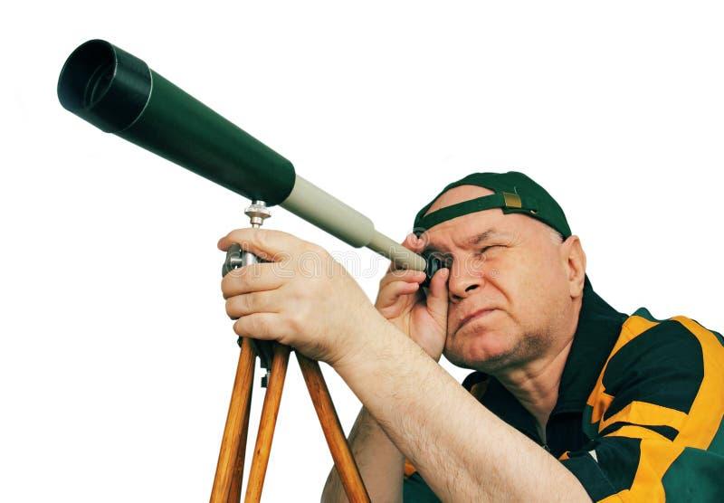 Uomo, un astronomo che osserva tramite un telescopio. fotografia stock