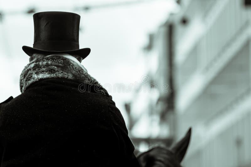 Uomo in un cappello che monta un cavallo immagine stock libera da diritti