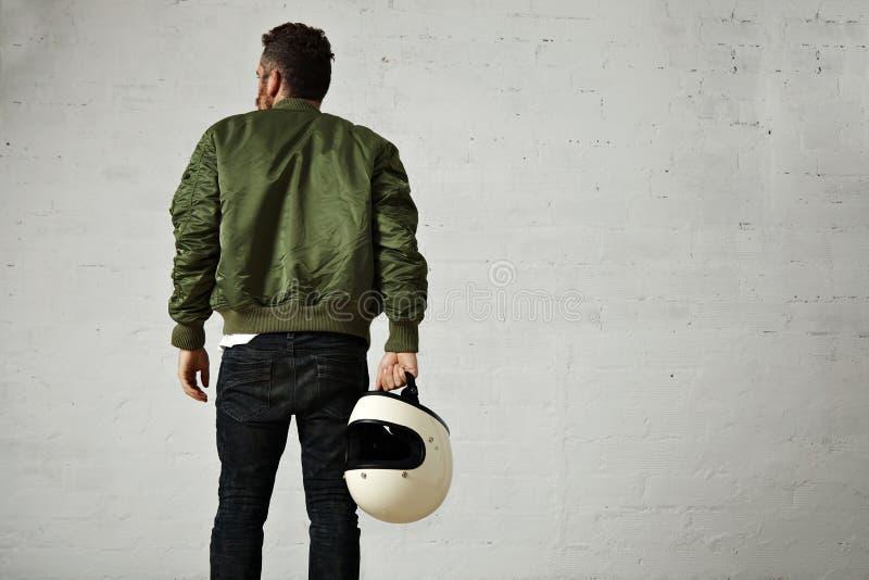 Uomo in un rivestimento pilota cachi con il casco fotografia stock