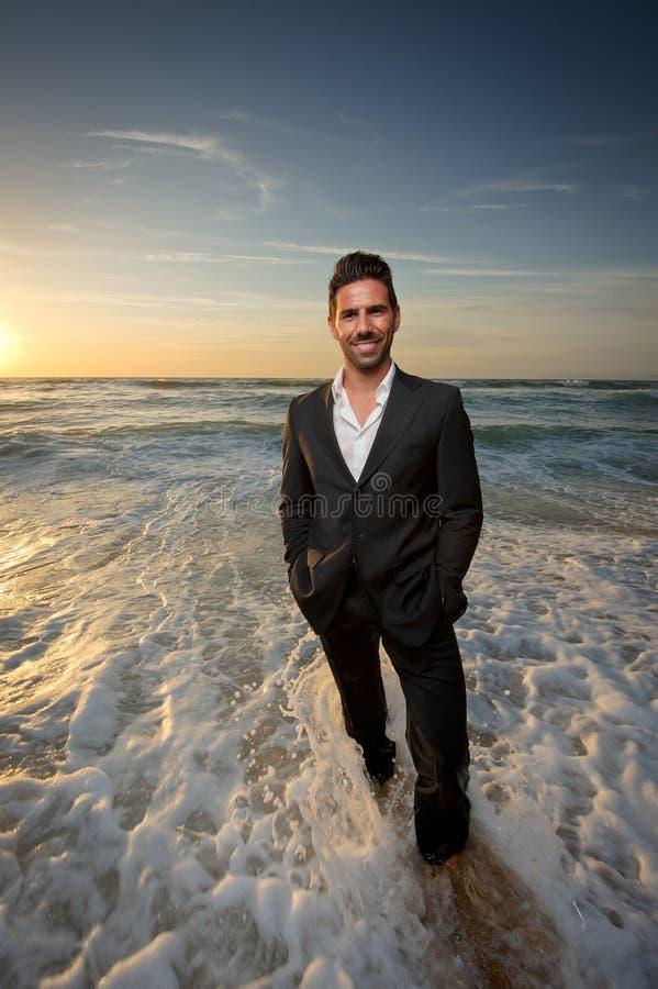 Uomo in un vestito alla spiaggia fotografia stock libera da diritti
