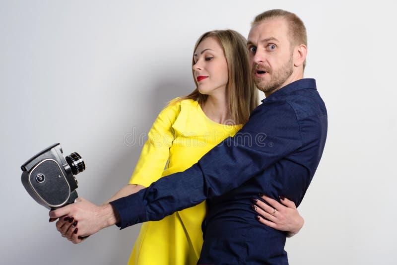 Uomo in una camicia blu ed in una giovane ragazza esile in un vestito giallo con la vecchia cinepresa immagini stock