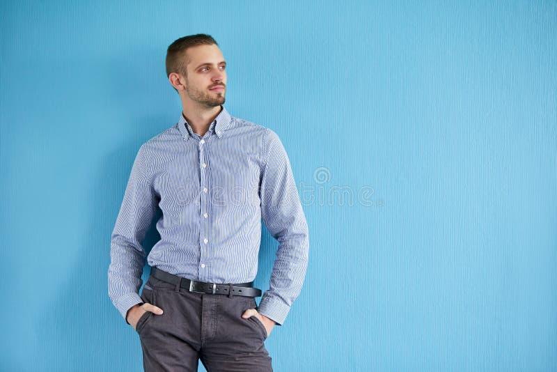 Uomo in una camicia su fondo blu fotografia stock