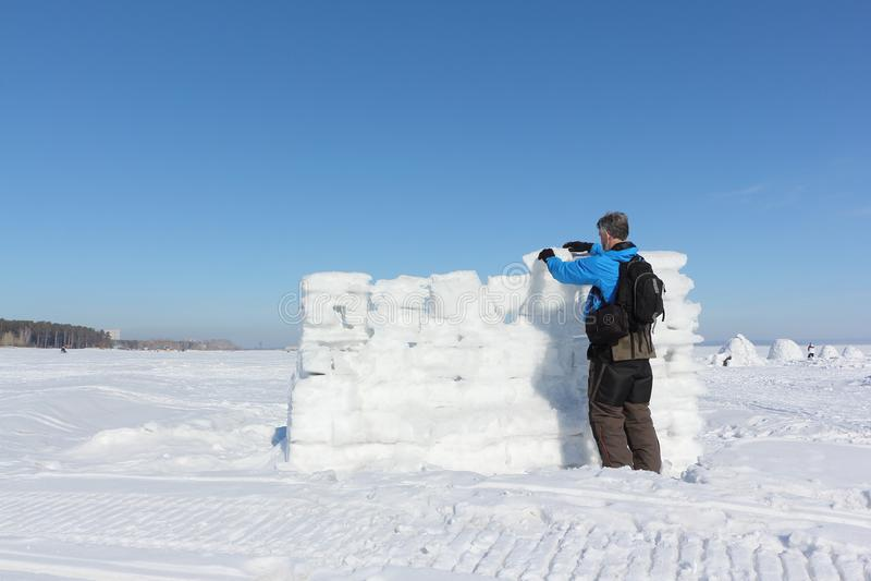 Uomo in una giacca blu che costruisce una parete della neve immagine stock