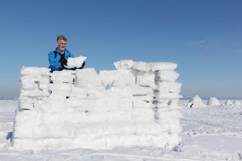 Uomo in una giacca blu che costruisce una parete della neve immagini stock