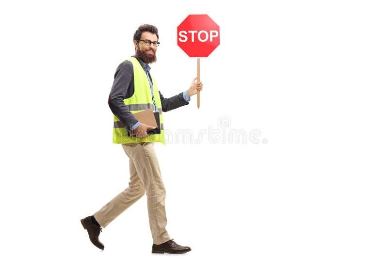 Uomo in una maglia di sicurezza che tiene camminata ed il gabinetto di un segnale stradale di arresto fotografie stock libere da diritti