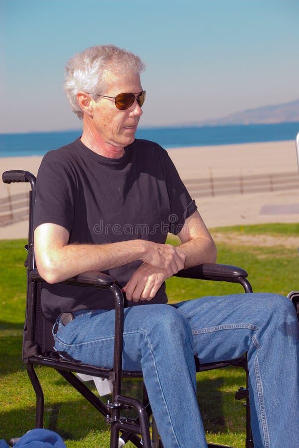 Uomo in una sedia a rotelle fotografia stock libera da diritti