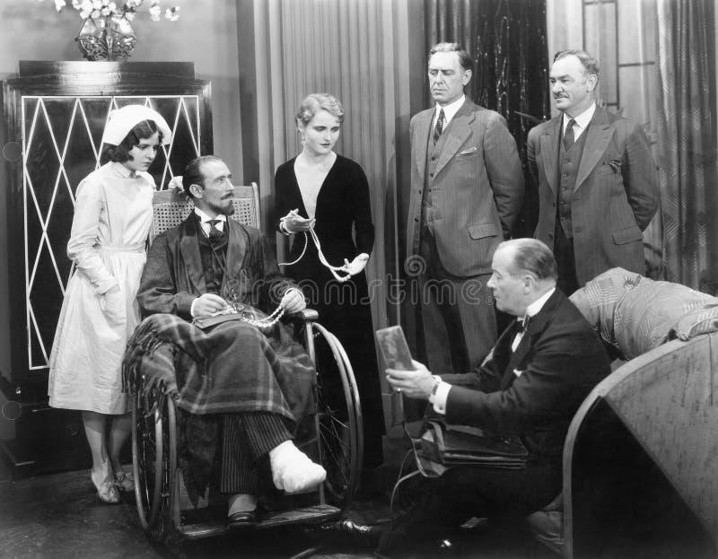 Uomo in una sedia a rotelle con un piede rotto e un gruppo di persone (tutte le persone rappresentate non sono vivente più lungo  immagini stock