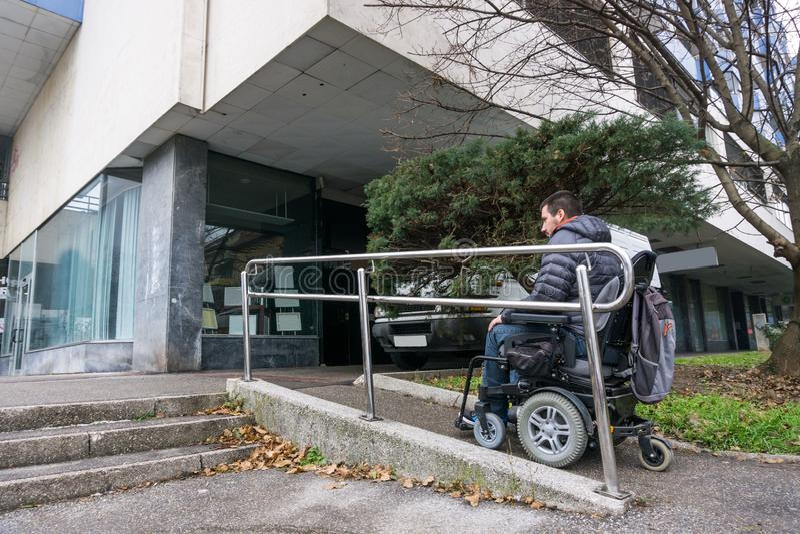 Uomo in una sedia a rotelle facendo uso di una rampa accanto alle scale immagini stock libere da diritti