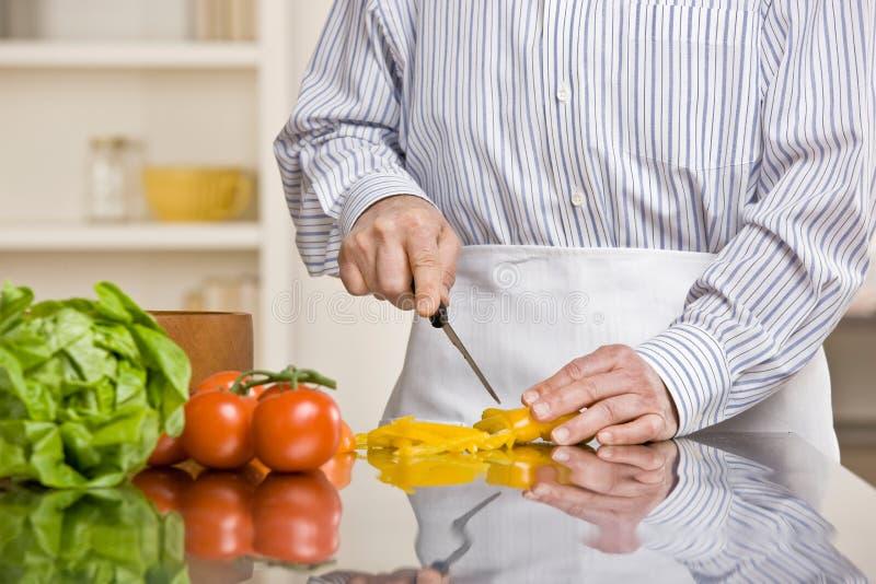 Uomo utile che prepara insalata in cucina fotografia stock