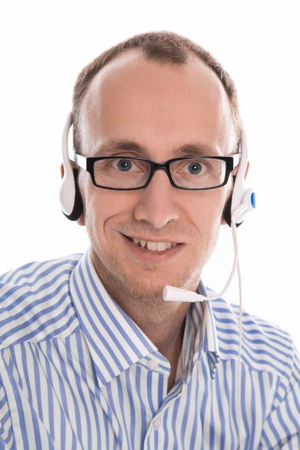 Uomo utile con la cuffia avricolare che sorride alla macchina fotografica. immagine stock libera da diritti