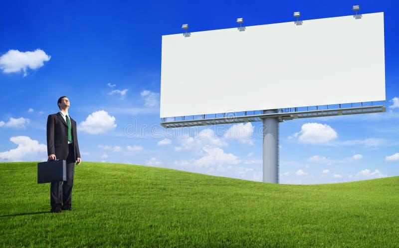 Uomo verde di affari di concetto e un tabellone per le affissioni vuoto fotografie stock libere da diritti