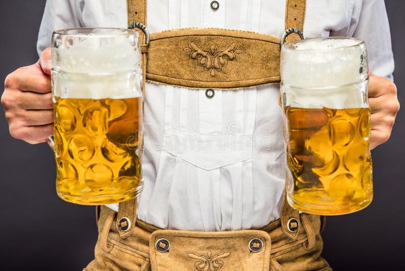 Uomo in vestiti bavaresi tradizionali che tengono tazza di birra fotografia stock