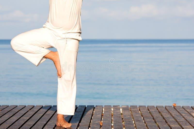 Uomo in vestiti bianchi che meditano yoga su pilastro di legno fotografie stock libere da diritti