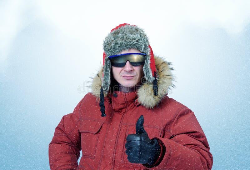 Uomo in vestiti ed occhiali da sole dell'inverno mostra il pollice fotografie stock