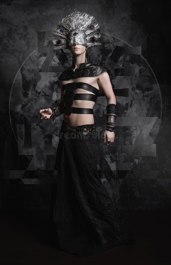 Uomo in vestiti scuri, demone con la maschera spaventosa fotografia stock