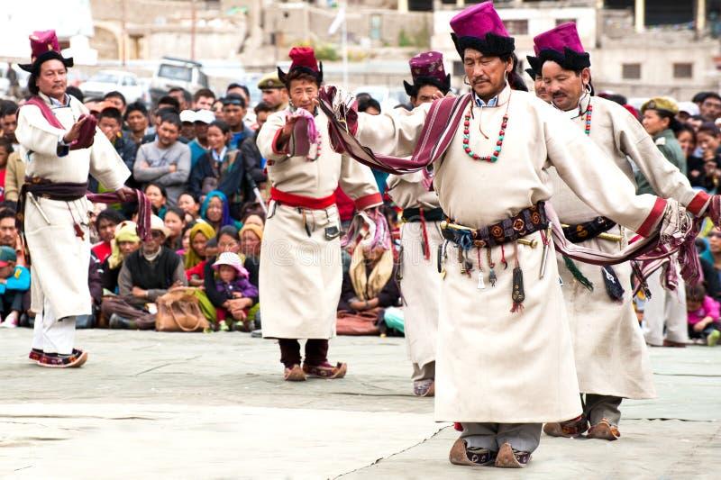 Uomo in vestiti tibetani che effettuano ballo di piega fotografia stock libera da diritti