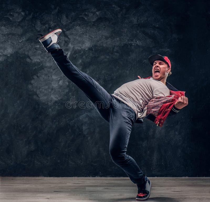 Uomo vestito alla moda emozionale che realizza i movimenti di break-dance sul pavimento fotografie stock libere da diritti