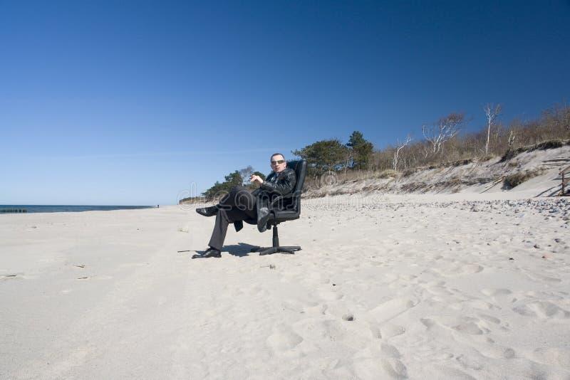Uomo in vestito che si distende sulla spiaggia fotografia stock libera da diritti