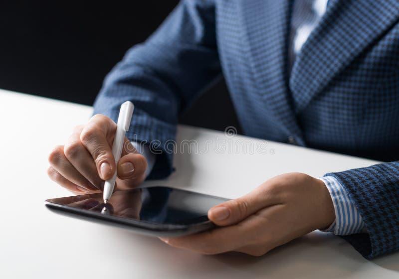 Uomo in vestito che si siede allo scrittorio con la compressa fotografie stock
