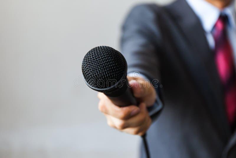 Uomo in vestito che tiene un microfono che conduce un affare immagine stock