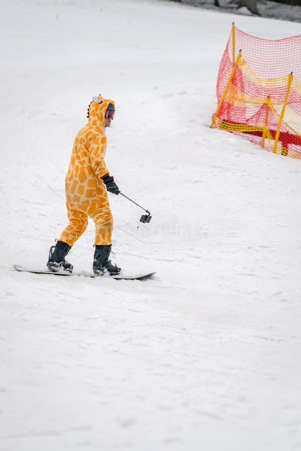 Uomo vestito come giraffa su uno snowboard fotografia stock
