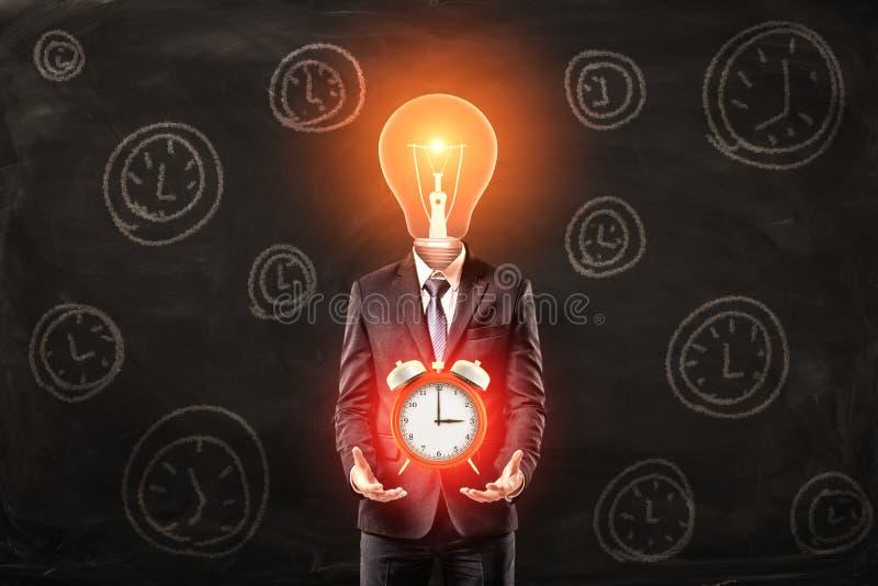 Uomo in vestito con della lampadina la testa invece, levitante grande sveglia rossa sopra le palme, stanti contro la parete nera  immagini stock
