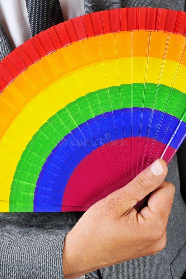 Uomo in vestito con un ventaglio dell'arcobaleno immagine stock libera da diritti