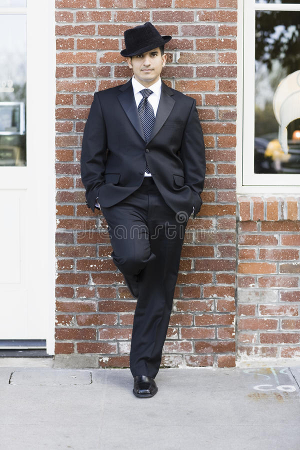 Uomo in vestito e legame che si appoggia contro la parete immagini stock libere da diritti