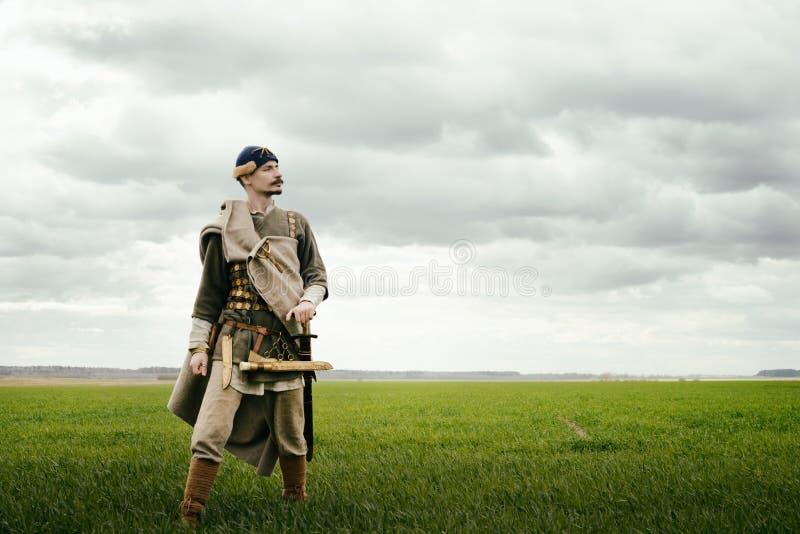 Uomo in vestito etnico nel contesto di ricostruzione storica fotografie stock