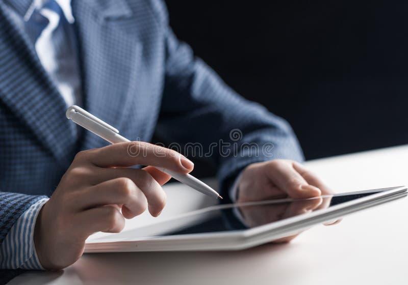 Uomo in vestito facendo uso del computer della compressa fotografia stock libera da diritti