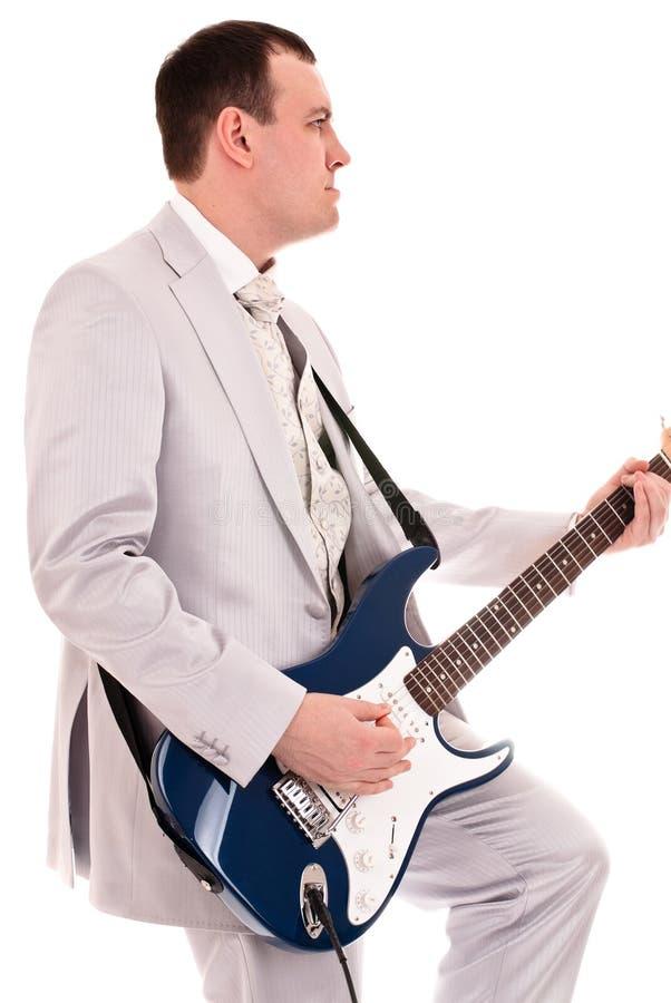 Uomo in vestito grigio che gioca chitarra fotografia stock libera da diritti