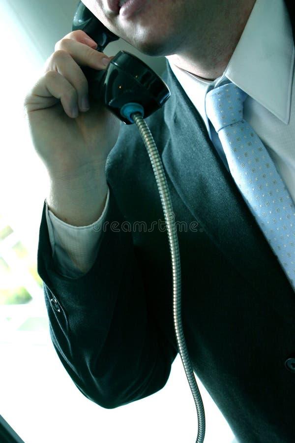 Uomo in vestito sul telefono a gettone immagine stock libera da diritti