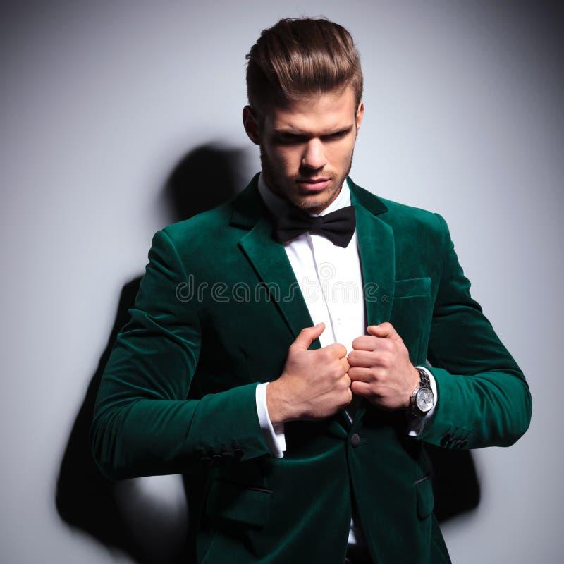 Uomo in vestito verde e farfallino che guarda poco un triste fotografie stock