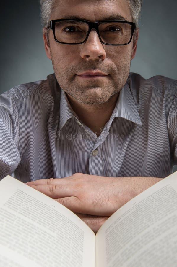 Uomo in vetri che si siedono alla tavola ed al libro di lettura fotografia stock libera da diritti