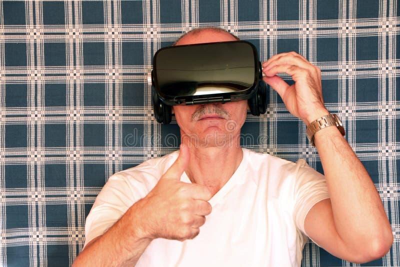 Uomo in vetri di realtà virtuale, fondo a quadretti blu fotografia stock