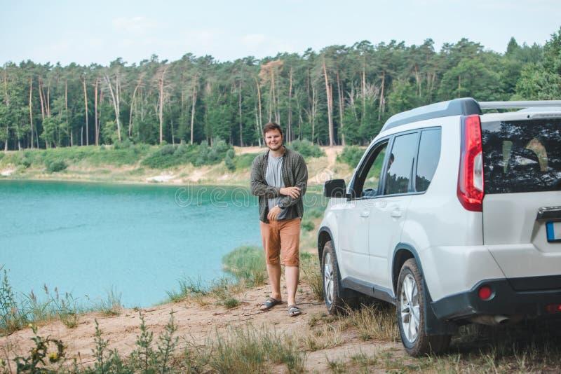 Uomo vicino all'automobile bianca del suv al bordo che esamina lago con acqua blu immagini stock